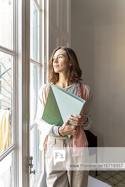 Woman holding folder looking out of window