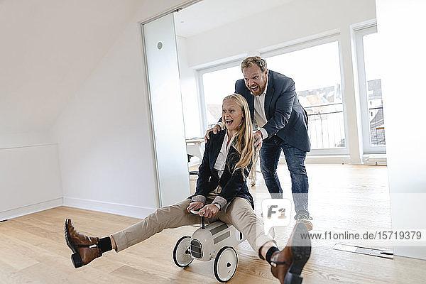 Verspielter Geschäftsmann drängt Geschäftsfrau auf Spielzeugauto im Büro