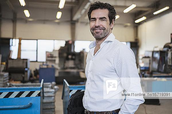 Porträt eines lächelnden Geschäftsmannes in einer Fabrik