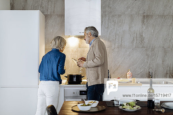 Reifere Paare bereiten das Abendessen zu Hause in der Küche zu Reifere Paare bereiten das Abendessen zu Hause in der Küche zu