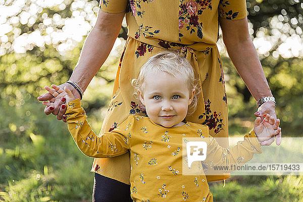 Porträt eines kleinen blonden Mädchens Hand in Hand mit ihrer Mutter auf einer Wiese