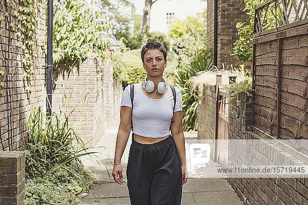 Porträt einer Frau mit Kopfhörer und Rucksack