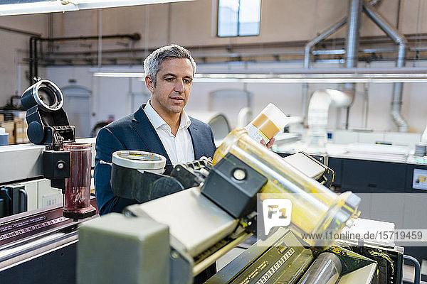 Geschäftsmann in einer Fabrik  der sich eine Maschine ansieht