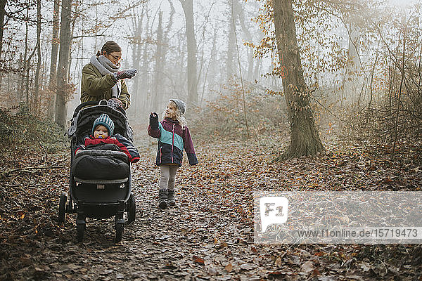 Mutter mit Töchtern beim Waldspaziergang im Herbst