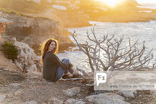 Rothaarige junge Frau sitzt bei Sonnenuntergang an der Küste  Ibiza  Spanien