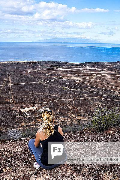 Rückansicht der auf dem Aussichtspunkt sitzenden Frau  Teneriffa  Spanien