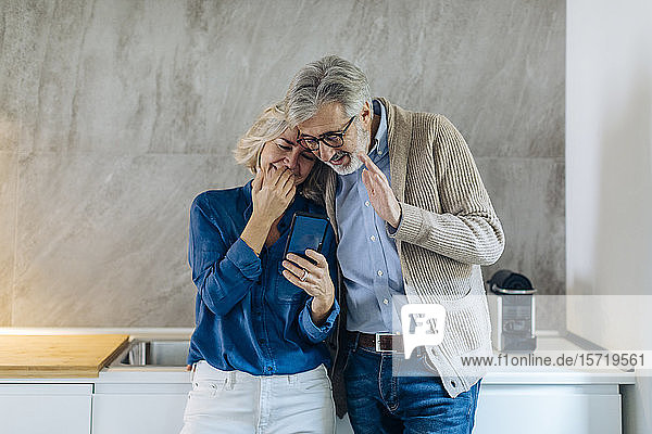 Mature couple using cell phone together in kitchen at home