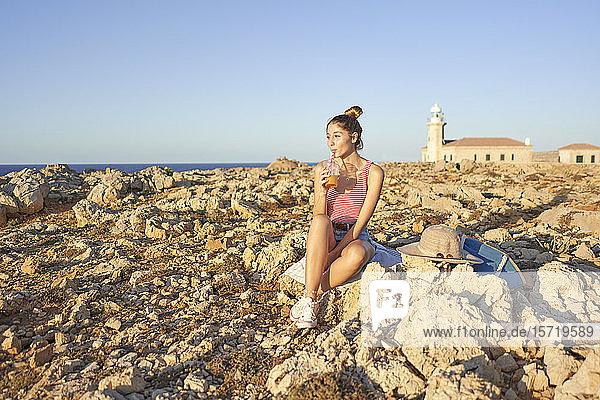 Junge Frau sitzt an felsigem Strand und entspannt sich  Menorca  Spanien