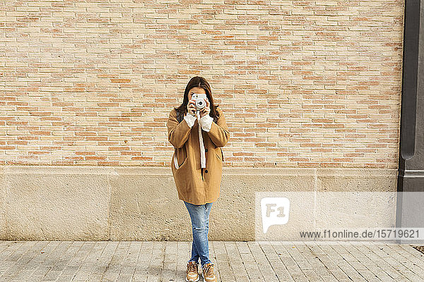 Young woman with camera taking pictures in front of a brick wall