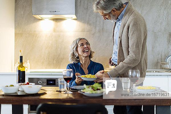 Reifer Mann serviert seiner glücklichen Frau zu Hause in der Küche das Abendessen Reifer Mann serviert seiner glücklichen Frau zu Hause in der Küche das Abendessen