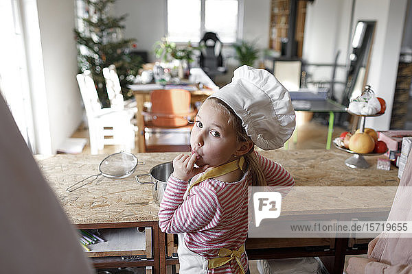 Girl wearing chef's hat in the kitchen
