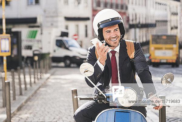 Junger Geschäftsmann mit Motorroller mit Mobiltelefon in der Stadt  Lissabon  Portugal