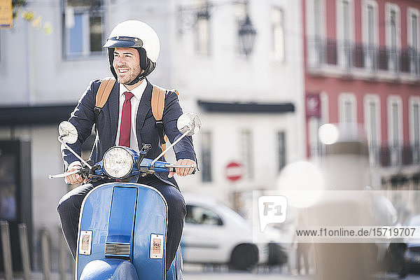 Young businessman riding motor scooter in the city  Lisbon  Portugal