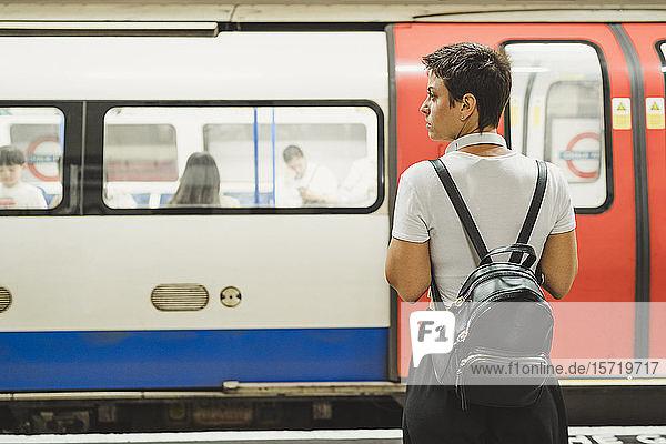 Rückenansicht einer Frau mit Rucksack  die auf dem Bahnsteig der U-Bahn-Station wartet  London  UK Rückenansicht einer Frau mit Rucksack, die auf dem Bahnsteig der U-Bahn-Station wartet, London, UK