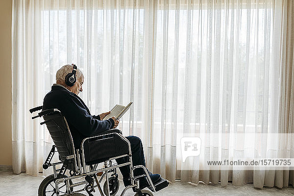 Senior man sitting in wheelchair reading a book while listening music with headphones