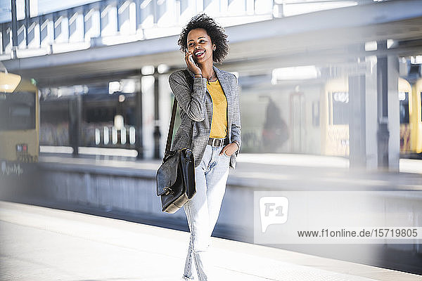 Glückliche junge Frau am Telefon auf dem Bahnhof
