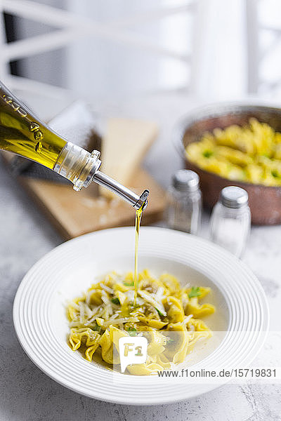 Olive oil pouring into plate of Italian tortellini with grana cheese