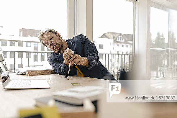 Businessman playing golf on desk in office