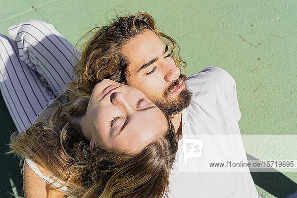 Junges Paar mit geschlossenen Augen entspannt sich Kopf an Kopf im Sonnenlicht