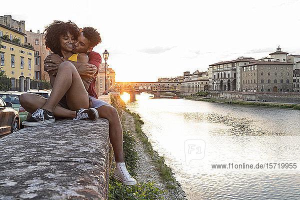 Liebenswertes junges Touristenpaar sitzt bei Sonnenuntergang auf einer Mauer am Arno  Florenz  Italien