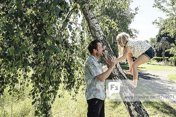 Father helping daughter climbing a birch trunk in park
