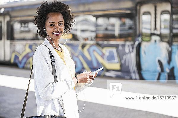 Porträt einer lächelnden jungen Frau mit Handy und Kopfhörer am Bahnhof