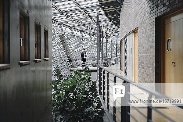 Geschäftsfrau  die auf einem Skywalk in einem modernen Bürogebäude steht