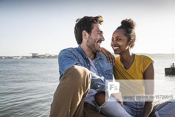 Glückliches junges Paar sitzt am Pier am Wasser  Lissabon  Portugal