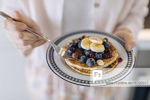 Nahaufnahme einer Frau  die einen Teller mit Pfannkuchen und Obst hält Nahaufnahme einer Frau, die einen Teller mit Pfannkuchen und Obst hält