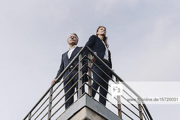 Geschäftsmann und Geschäftsfrau stehen auf einem Balkon
