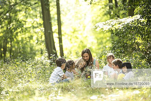 Lehrerin sitzt mit Schulkindern im Wald und erzählt Geschichten
