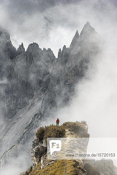 Bergsteiger steht auf einem Grat  hinten Berggipfel und spitze Felsen  dramatische Wolken  Cimon di Croda Liscia und Cadini-Gruppe  Auronzo di Cadore  Belluno  Italien  Europa