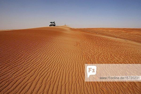 Geländewagen und Tourist auf einer Sanddünen  Wüstensafari  Wüste Rimal Wahiba Sands  Oman  Asien