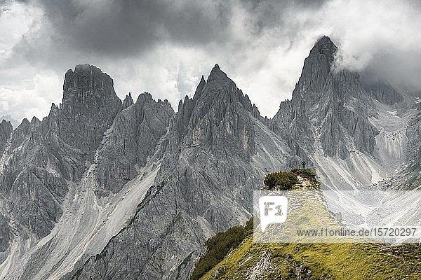 Frau steht auf einem Grat  hinten Berggipfel  Felsenkamm mit spitzen Felszacken  dramatische Wolken  Cimon di Croda Liscia und Cadini-Gruppe  Sextener Dolomiten  Belluno  Italien  Europa
