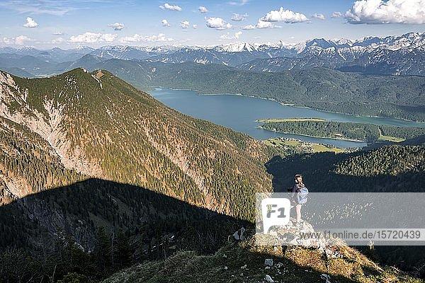 Wanderin blickt über Berglandschaft und Walchensee  Wanderweg  Herzogstand Heimgarten Überschreitung  Oberbayern  Bayern  Deutschland  Europa