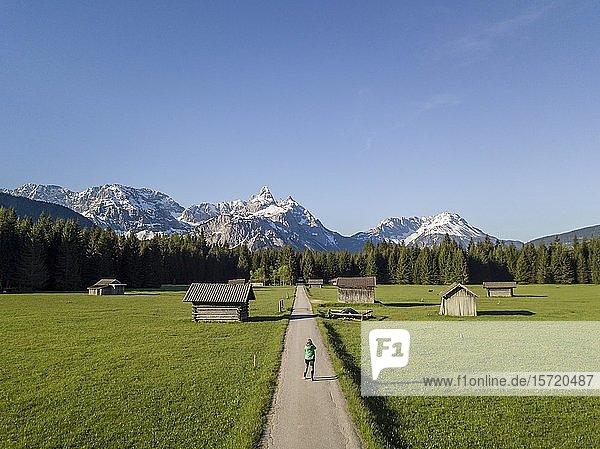 Wanderin auf einem Weg  Heustadl auf einer Wiese  Ehrwalder Sonnenspitz und Berge  bei Ehrwald  Mieminger Kette  Tirol  Österreich  Europa