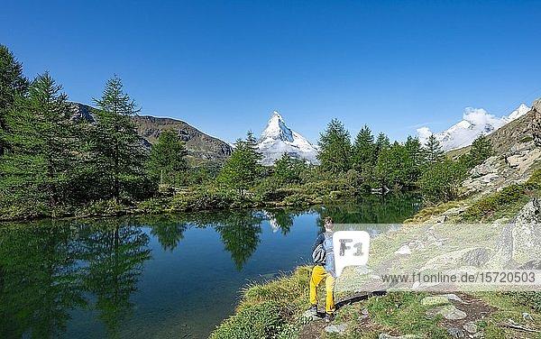 Wanderer am Grindijsee  hinten schneebedecktes Matterhorn  5-Seen-Wanderweg  Wallis  Schweiz  Europa