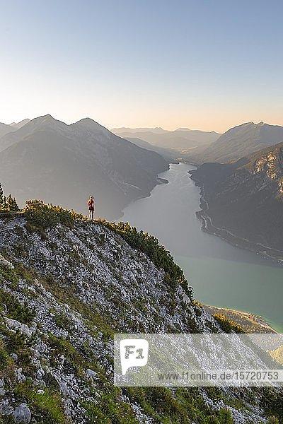 Junge Frau blickt über Berglandschaft  Ausblick vom Berg Bärenkopf auf den Achensee  links Seebergspitze und Seekarspitze  Tirol  Österreich  Europa