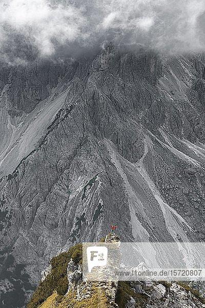 Frau steht auf einem Grad  hinten Felsen  dramatische Stimmung  hinten Bergfuß des Cimon di Croda Liscia  Auronzo di Cadore  Belluno  Italien  Europa