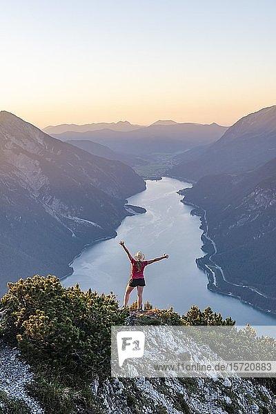 Sonnenuntergang  junge Frau streckt Arme in die Luft  Ausblick vom Berg Bärenkopf auf den Achensee  links Seebergspitze und Seekarspitze  rechts Rofangebirge  Tirol  Österreich  Europa