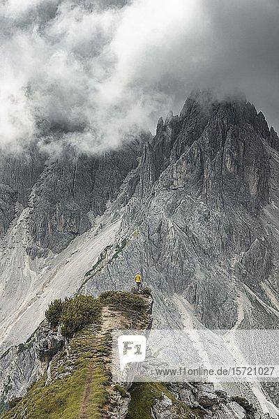 Frau in gelber Jacke steht auf einem Grat  hinten Berggipfel und spitze Felszacken  dramatische Wolken  Cimon die Croda Liscia und Cadini-Gruppe  Auronzo di Cadore  Belluno  Italien  Europa