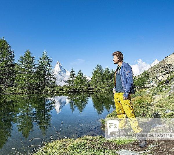 Hiker on Lake Grindij  snow-covered Matterhorn reflected in the lake  5 lake hiking trail  Valais  Switzerland  Europe