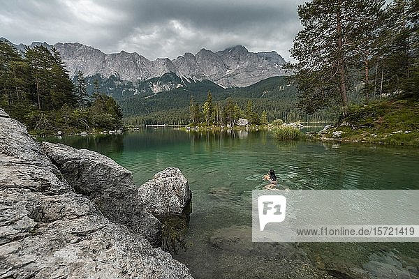 Woman swimming in the lake  view of Eibsee lake in front of Zugspitze massif with Zugspitze  cloudy  Wetterstein range  near Grainau  Upper Bavaria  Bavaria  Germany  Europe