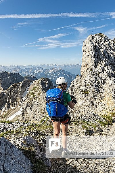 Bergsteigerin mit Rucksack blickt über Berge  Mittenwalder Höhenweg  Karwendelgebirge  Mittenwald  Deutschland  Europa