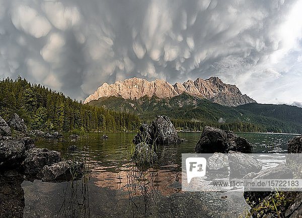 Rocks on the shore  Eibsee lake in front of Zugspitze massif with Zugspitze  sunset  dramatic Mammaten clouds  Wetterstein range  near Grainau  Upper Bavaria  Bavaria