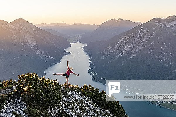Sunset  young woman stretches arms in the air  view from the mountain Bärenkopf to Lake Achensee  left Seebergspitze and Seekarspitze  right Rofan Mountains  Tyrol  Austria  Europe