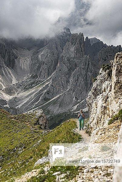 Junge Frau  Bergsteigerin auf einem Wanderweg  hinten Berggipfel und spitze Felszacken  Wolkenhimmel  Cimon di Croda Liscia und Cadini-Gruppe  Sextener Dolomiten  Belluno  Italien  Europa