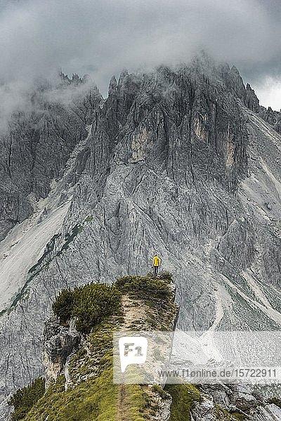 Frau in gelber Jacke steht auf einem Grat  hinten Berggipfel und spitze Felszacken  Wolkenhimmel  Cimon die Croda Liscia und Cadini-Gruppe  Auronzo di Cadore  Belluno  Italien  Europa