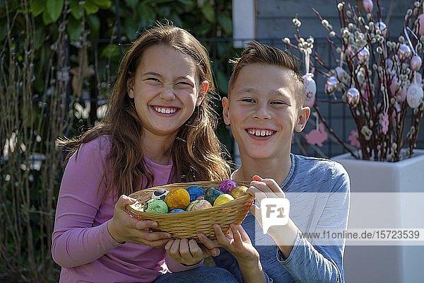 Geschwister  Mädchen und Junge freuen sich über Körbchen mit bemalten Ostereiern  Bayern  Deutschland  Europa