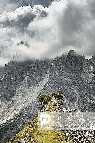 Frau in gelber Jacke steht auf einem Grat  hinten Felswand  dramatische Wolken  Cimon die Croda Liscia und Cadini-Gruppe  Auronzo di Cadore  Belluno  Italien  Europa